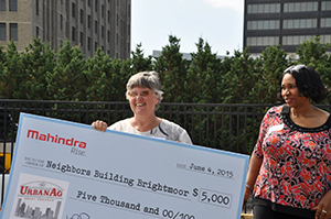 Riet Schumack (left) holds a check donation to the organization she helped cofound, Neighbors Building Brightmoor. (photo courtesy of Riet Schumack)