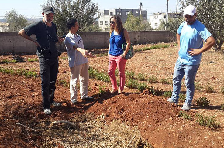Ecological gardens in Farkha with guests and the agroecology coordinator © Photo: Saad Dagher